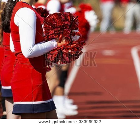 Sunlight Reflects Off Of The Red Pom Poms That Cheerleaders Are Holding While Standing On A Track Wa