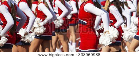 High School Cheerleaders With Red And Whte Pom Poms Are Synchronized While Cheering At Their School