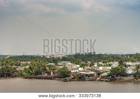 Long Tau River, Vietnam - March 12, 2019: Riverside Phuoc Khanh Village With Multiple Houses. Light
