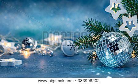 Silver Glass Ball, Jingle Bells And Glowing Star Lights Garland. Green Christmas Tree Branch On Blur