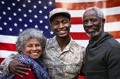 Portrait of a young adult African American male soldier embracing with his parents, all of them smiling to camera in front of a US flag poster
