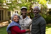 Portrait of a young adult African American male soldier in the garden outside his home embracing with his parents, all of them smiling to camera poster