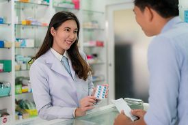 Confident Asian Young Female Pharmacist With A Lovely Friendly Smile And Explaining Capsule Medicine