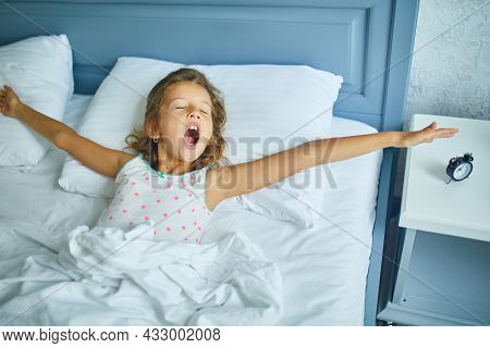 Little Girl Wakes Up From Sleep On A Big And Cozy Bed White Linen In The At Home