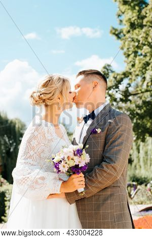 Young Married Couple Kissing, Groom In Suit Embraces Beautiful Bride In White Dress With Bouquet, We