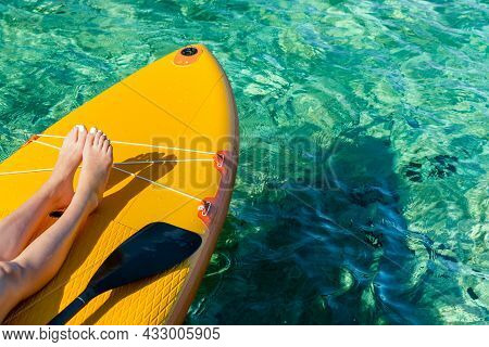 Orange Stand Up Paddle Board With Visible Legs Of A Young Girl And A Paddle On The Turquoise Surface