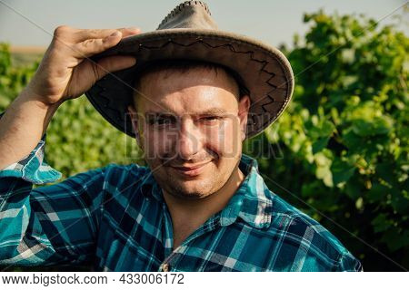 Cheerful Man With Modern Young Winemaker Hat Is On The Vineyard. The Portrait Of The Winemaker Looki