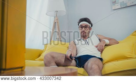 Dissatisfied Man In Retro Sportswear Sitting On Sofa And Watching Tv