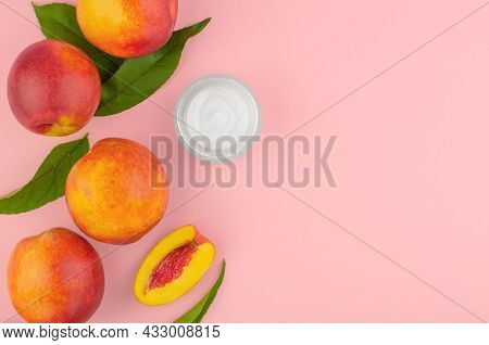 Natural Cosmetics From Peaches. Body Cream And Fresh Peaches On A Pink Background. An Open Jar Of Bo