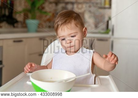 Happy Cute Infant Baby Boy Eats Itself. Caucasian Little Baby Boy With Funny Face Concentrated On Fo