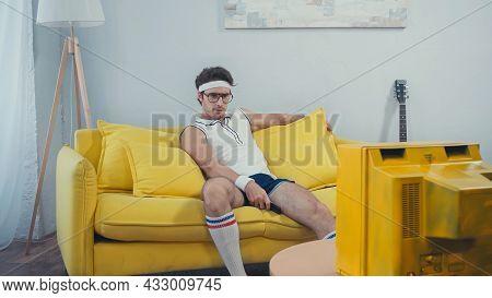 Lazy Man In Sportswear Watching Retro Tv Sitting On Sofa In Living Room