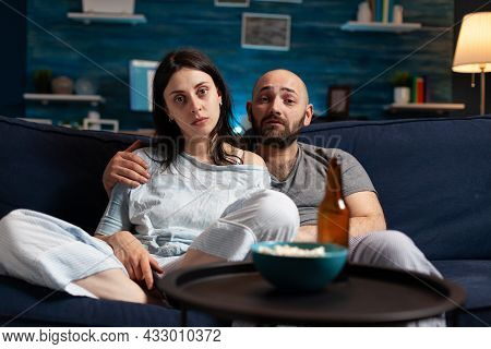 Confused Astonished Young Couple Watching Documentary Show Having Shocked Facial Expression, Eating