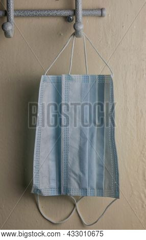 Face masks or surgical masks are hanged on metal hanger on yellow wall background