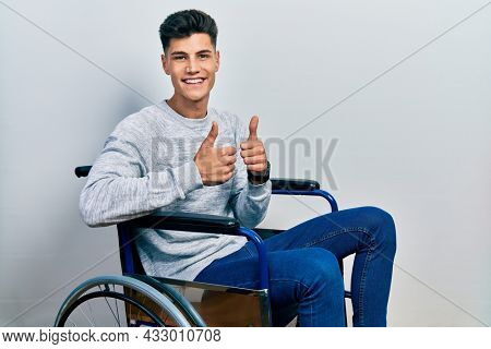 Young hispanic man sitting on wheelchair success sign doing positive gesture with hand, thumbs up smiling and happy. cheerful expression and winner gesture.