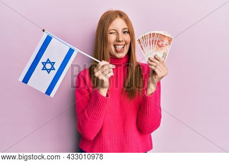 Young irish woman holding israel flag and shekels banknotes sticking tongue out happy with funny expression.