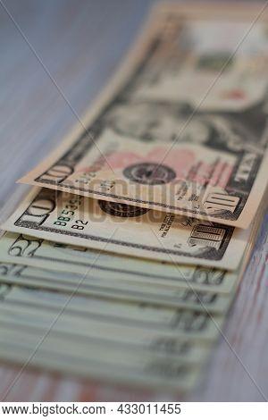 Ten And Twenty Dollar Bills On A Wooden Light Background. Shallow Depth Of Field