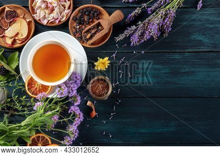Herbal Tea, Top Shot With Copy Space. Herbs, Flowers And Fruit Around A Cup Of Tea On A Dark Rustic