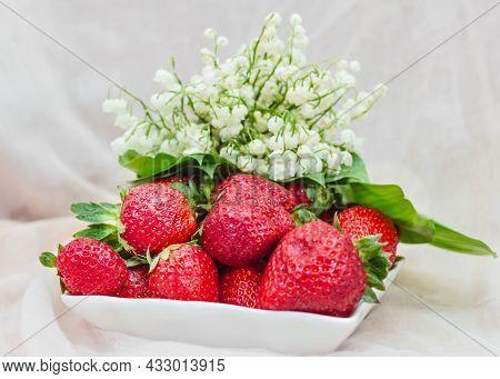 Fresh Ripe Red Strawberries And Spring Soft White Lilies Of The Valley