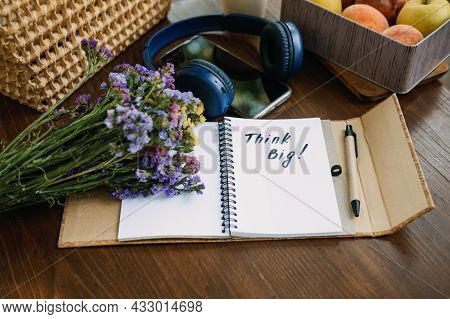 Think Big Motivational Phrase In Open Notebook On The Table. Outdoor Still Life With Think Big Motiv