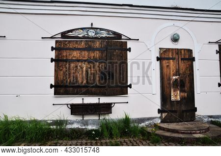 Large Wooden Shutters On The Old Building. Shutters With Metal Stripes And A Wooden Door In The Hous