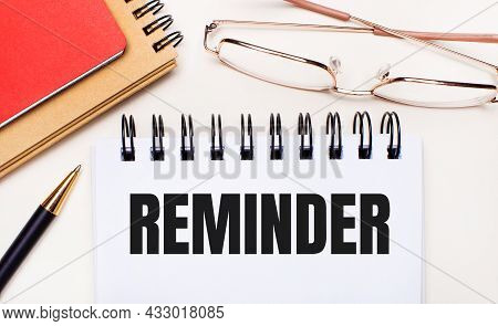 On A Light Background - Glasses In Gold Frames, A Pen, Brown And Red Notepads And A White Notebook W