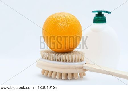 Orange On Double-sided Manual Massage Brush For Body And Body Cream With Dispenser On White Backgrou