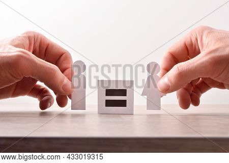 Gender Equality Concept With Hands Catching Cutouts Shaped Like Man And Woman Holding Sign With Equa
