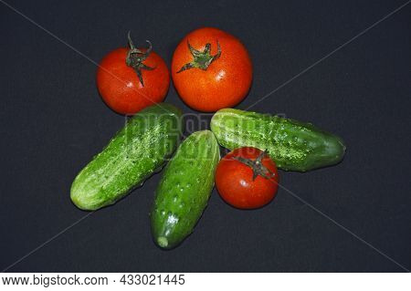 Ripe Vegetables: Green Cucumbers And Red Tomatoes On A Black Background, The Concept Of Proper And H
