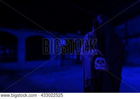 Horror Scene Of Scary Mysterious Black Man Holding A Skull In His Hand At A Creepy Old Building Corr