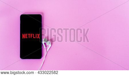 Bangkok, Thailand - September 6, 2021: Mobile Phone With Earphones Connected To Netflix Media With P