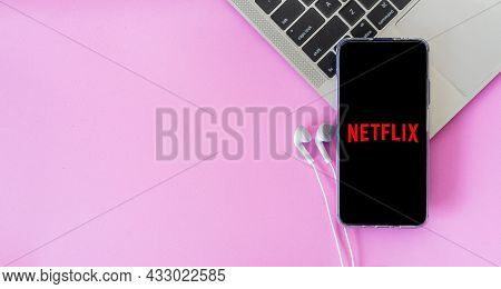 Bangkok, Thailand - September 6, 2021: Mobile Phone With Earphones Connected To Netflix Media Placed