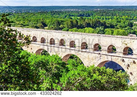 The Pont du Gard is the tallest Roman aqueduct. The aqueduct Pont du Gard connects hills covered with dense deciduous forest. The Gardon River in sunny day. Interesting trip to France.