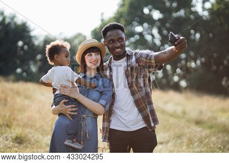 Positive Multiracial Family Of Three Spending Summer Time On Nature And Taking Selfie For Saving Mem