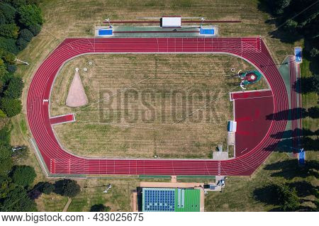 An Aerial View Of An Outdoor Athletics Stadium With Red, Oval Running Track And Facilities For Sport
