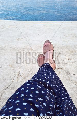 Female Feet Seen From Above. Selfie For Any Use. Foot And Legs In Sandals. Girl Sitting By The Seash