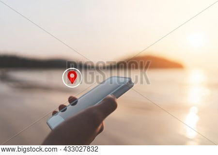 Woman Hand Using Smart Phone With Navigator Location Point At Tropical Sunset Beach Abstract Backgro