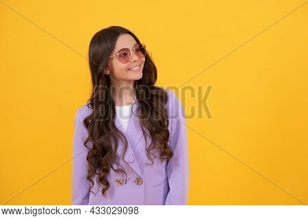Pretty Look Of Young Girl In Jacket. Portrait Of Happy Child On Yellow Background.