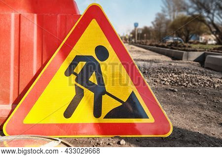 The Warning Sign For Road Repair Work Lies On The Roadway.