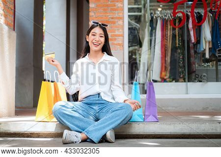 Asian Shopaholic Woman Wearing Sunglass Headband With Many Colorful Shopping Bags And Holding Credit