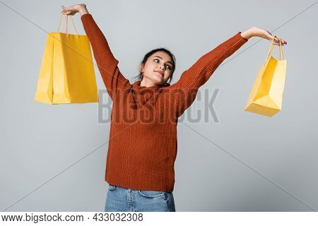 Pleased Young Woman In Sweater And Jeans Holding Yellow Shopping Bags Isolated On Grey