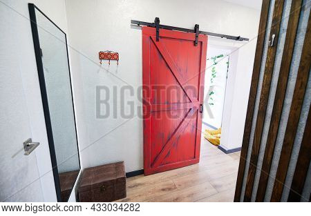 View Of Red Door In Corridor With Big Mirror On Wall And Ottoman. Interior Of Hallway Of Appartment