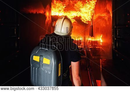 Volunteer Firefighter Enters Burning Room During An Exercise To Extinguish Fire And Save People. Fir