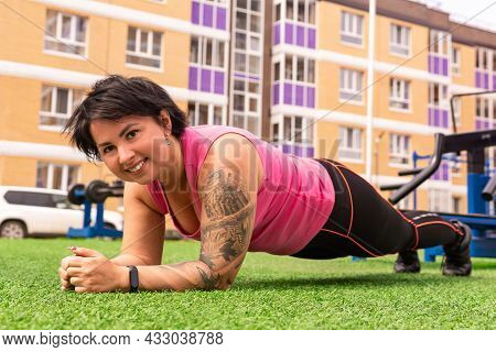 Muscular Plump Woman Exercising On The Sports Ground