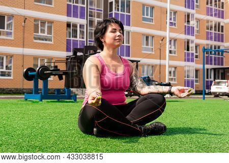Young Sturdy Chubby Woman Meditates On The Lawn After Exercising In The Courtyard Of A City House Ag