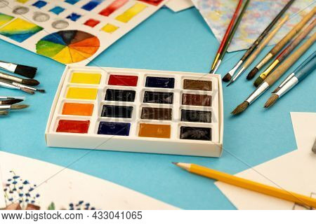A Box Of Watercolors With Brushes. Draw, Background. Packing Of Multicolored New Paints On The Table