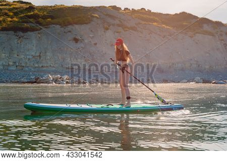 May 28, 2021. Anapa, Russia. Young Girl On Stand Up Paddle Board With Morning Light. Woman Vacation
