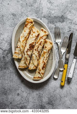 Crepes Stuffed With Tuna, Avocado And Egg On A Grey Background, Top View