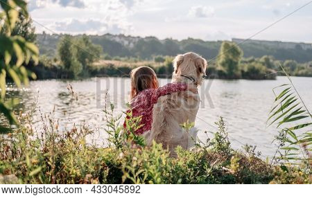 Child girl sitting and hugging golden retriever dog outdoors at the nature and looking at the lake. Teen kid with doggy pet resting close to river