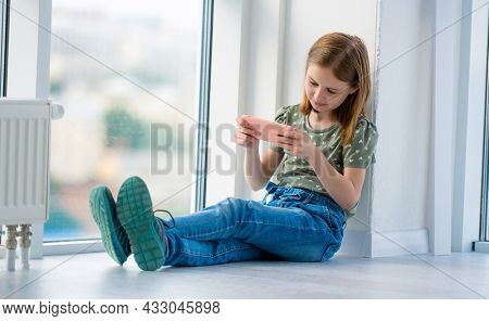 Preteen girl sitting on windowsill with smartphone and looking at display. Beautiful female kid schoolgirl reading from cell phone at home