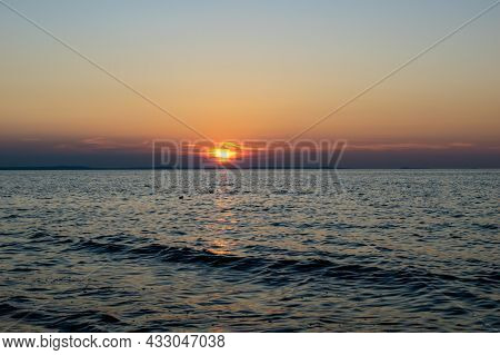 The Setting Sun Against The Backdrop Of A Calm Sea